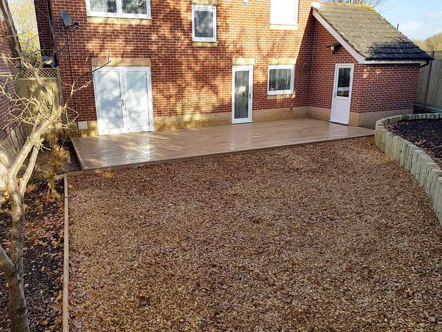 The completed rear garden makeover featuring new fencing with timber retaining walls and decorative gravel and feature composite deck in Golden Oak colour